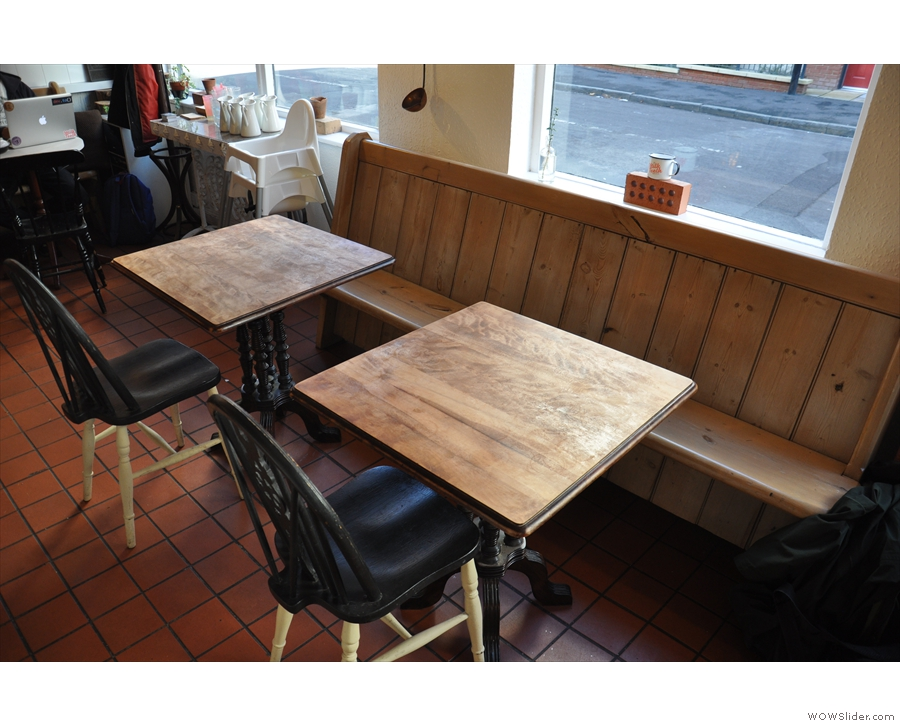 There's a second wooden bench a little further on, with square tables this time.