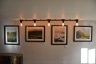 ... which is decorated with lots of pictures and illuminated with rows of bare light bulbs.