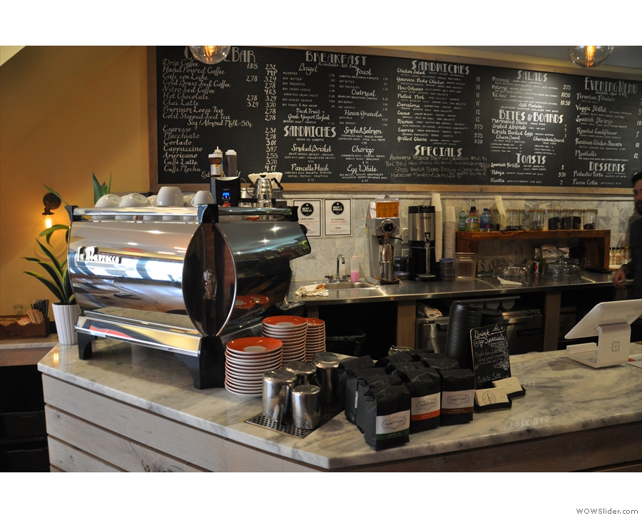 The counter is on the left, at the back, starting with the coffee.