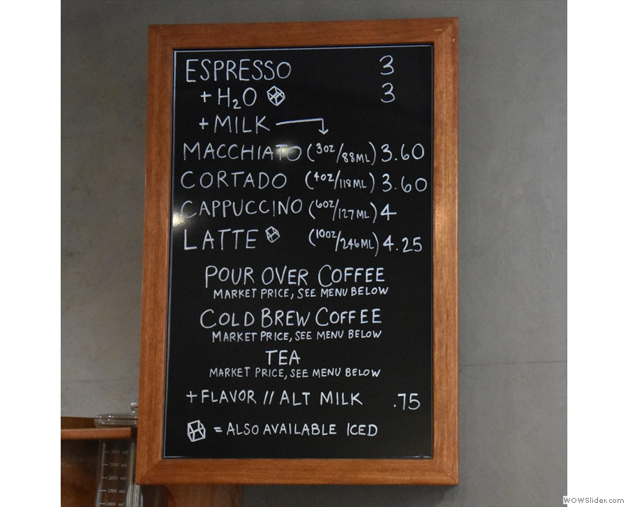 The concise coffee menu is on the wall to the right of the till...
