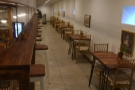 The view back along the balcony, a row of stools on one side and tables on the other.