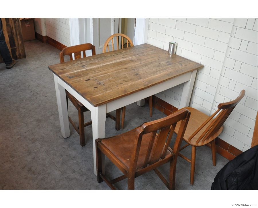There are also some tables against the back wall. A four-person one stands by the door...