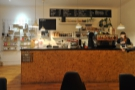 The till's at the front end of the counter, while the espresso machine and twin grinders...