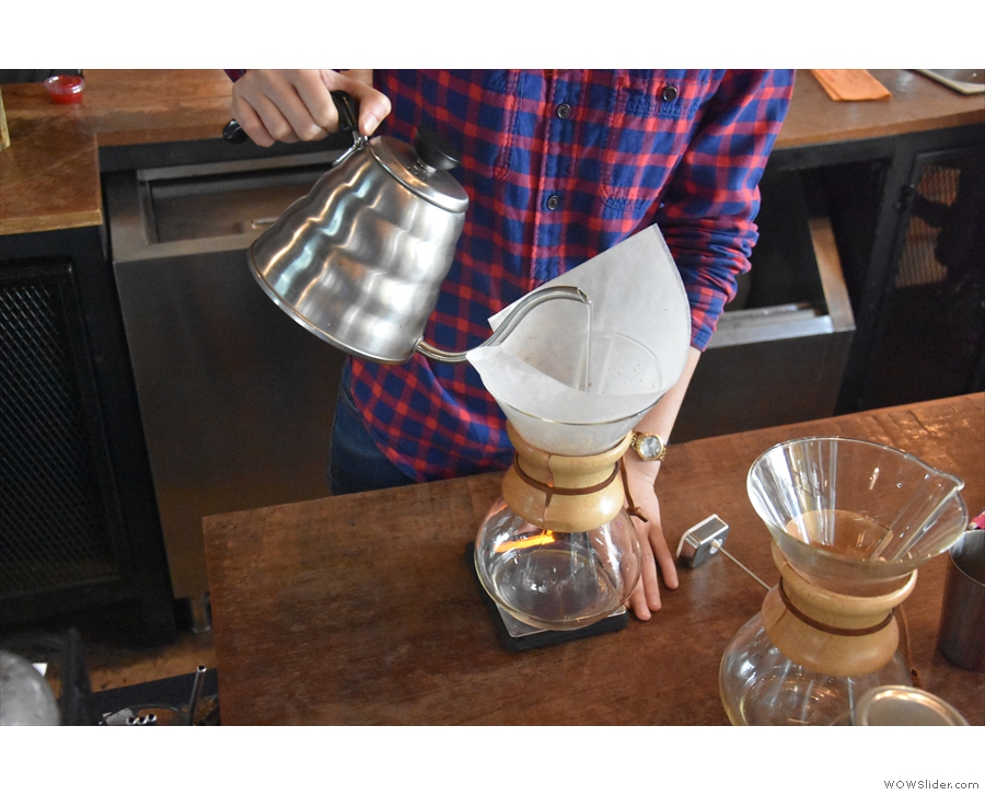 The barista employs a steady, slow pour, moving the tip of the kettle around the filter.