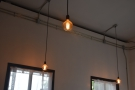 These exposed light bulbs hang down from the high ceiling.