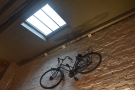 There's a bicycle high up on the back wall of the back room, hanging under the skylight.