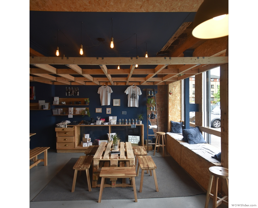 This is followed by a communal table in the centre of the space, retail shelves behind...