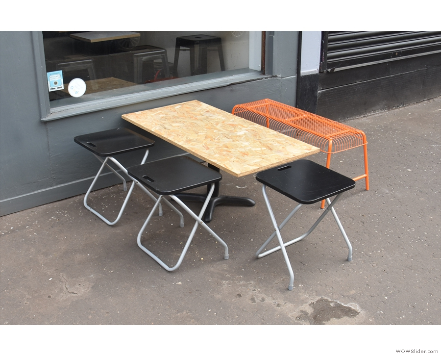 The broad pavement has plenty of space for this large chipboard table.