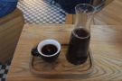 ... served in a carafe with a cup on the side, all presented on a wooden tray.