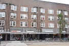 In West Amsterdam, on Jan Evertsenstraat, a parade of shops under a block of flats...