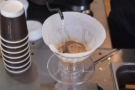 The pour is a controlled one, moving the spout across the surface of the coffee.