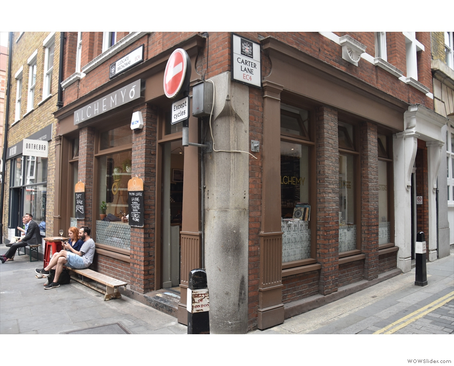 A narrow bench sits outside on Ludgate Broadway, with a small table to its right...