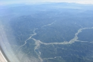 We're flying over a landscape of forested mountains and twisting valleys, with both...
