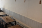 ... in the shape of a long bench, lined with four narrow tables...