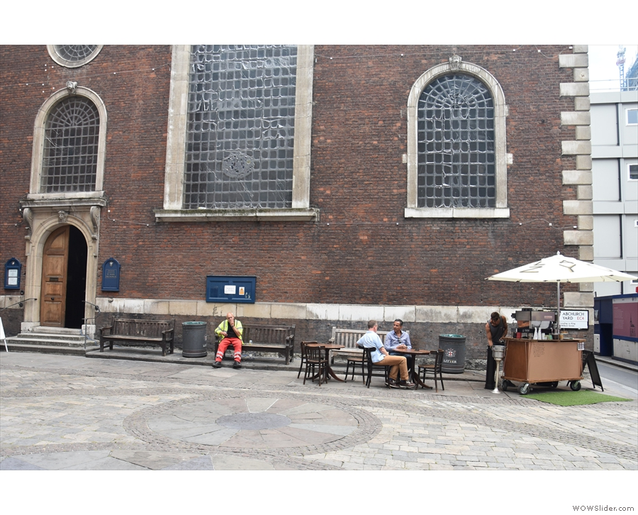 The cart is on the right, with some seating, including benches by the church & two tables.