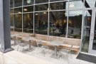 The outside seating in more detail: a wooden bench with a series of metal tables...