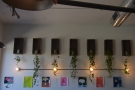 Various works of art, plus some interesting light-fittings, hang on the wall above the bench.
