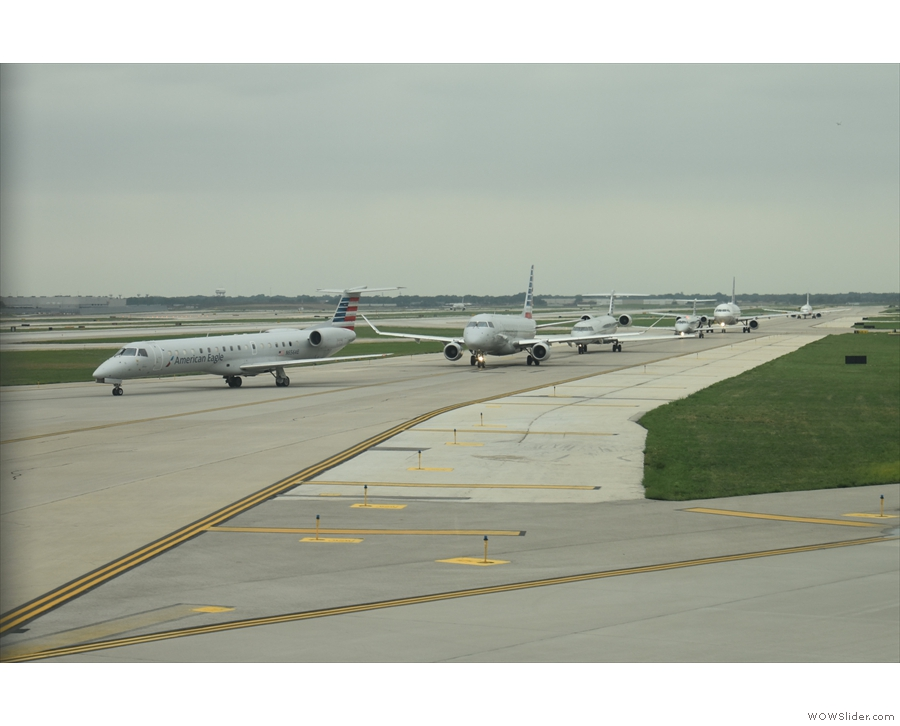 A queue of American Airlines planes waiting to take off.
