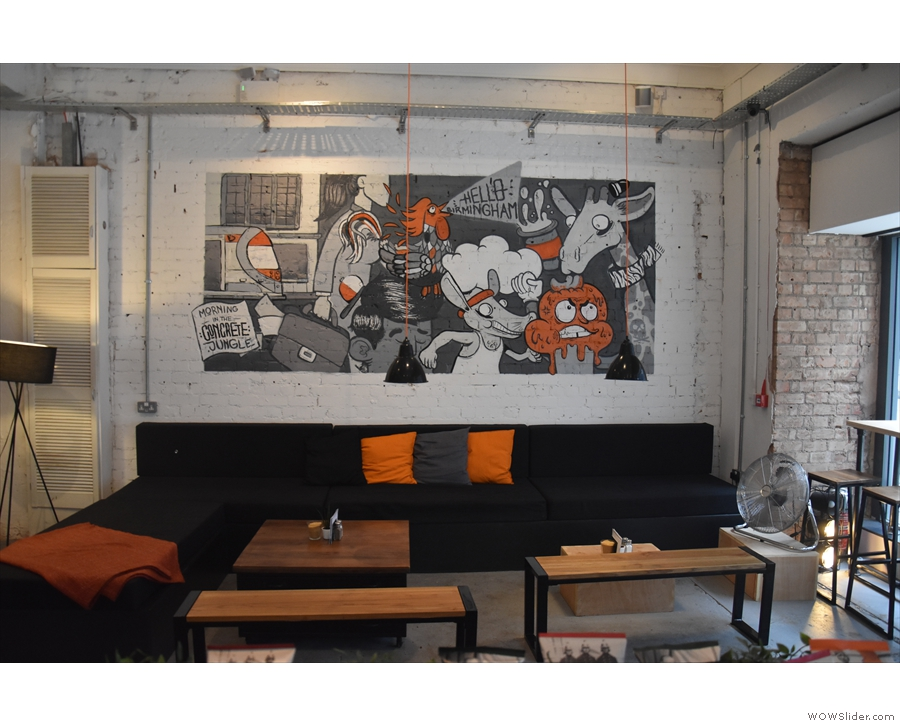 Another view of the sofas, with a mural on the wall behind and a pair of benches in front.