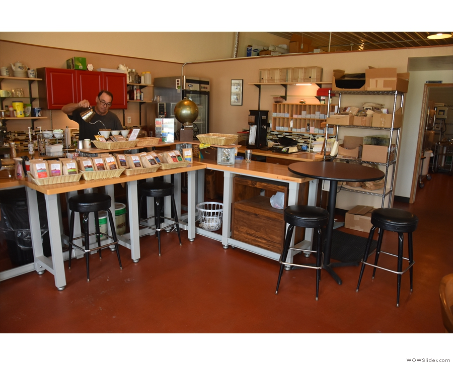 The counter is on the left. There are a couple of stools here, with a table at the end.