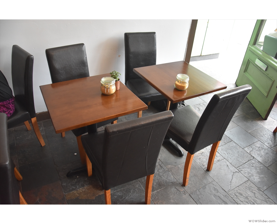 The seating's around the edges, starting with these two tables to the right of the door.