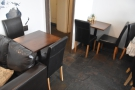 ... wiith a pair of two-person tables flanking the door to the kitchen (which is in the corner).