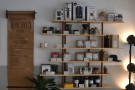 Meanwhile, ono the wall next to the counter is a large set of retail shelves, where...