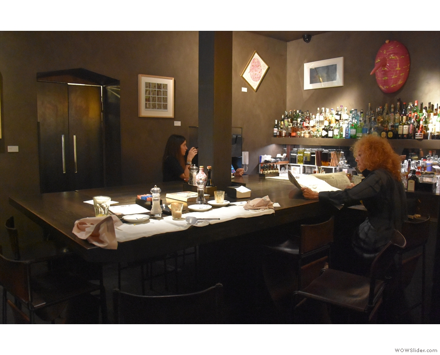 ... you'll find a roughly cube-shaped, cosy back room with a U-shaped table.