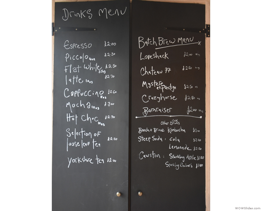 A simple menu is chalked on the wall behind the counter.