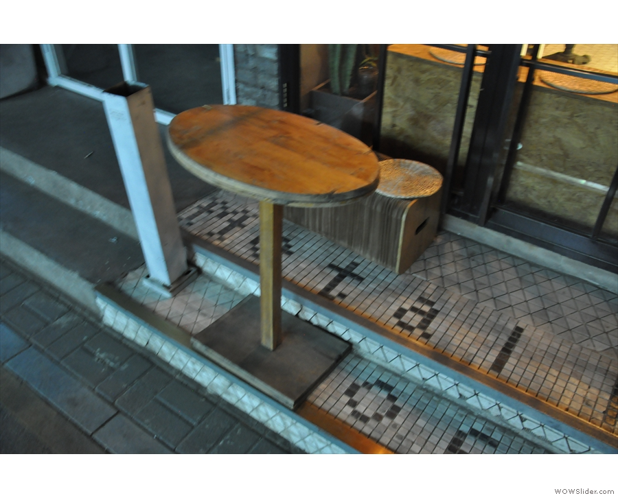 There is a bench outside, with a table. The steps say 'Metal Hands Coffee Co'.