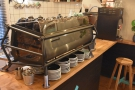 The espresso machine, an impressive-looking Sanremo Cafe Racer, is in the middle...
