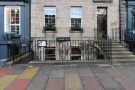 On George Street, in Edinburgh, iron railings fence off...