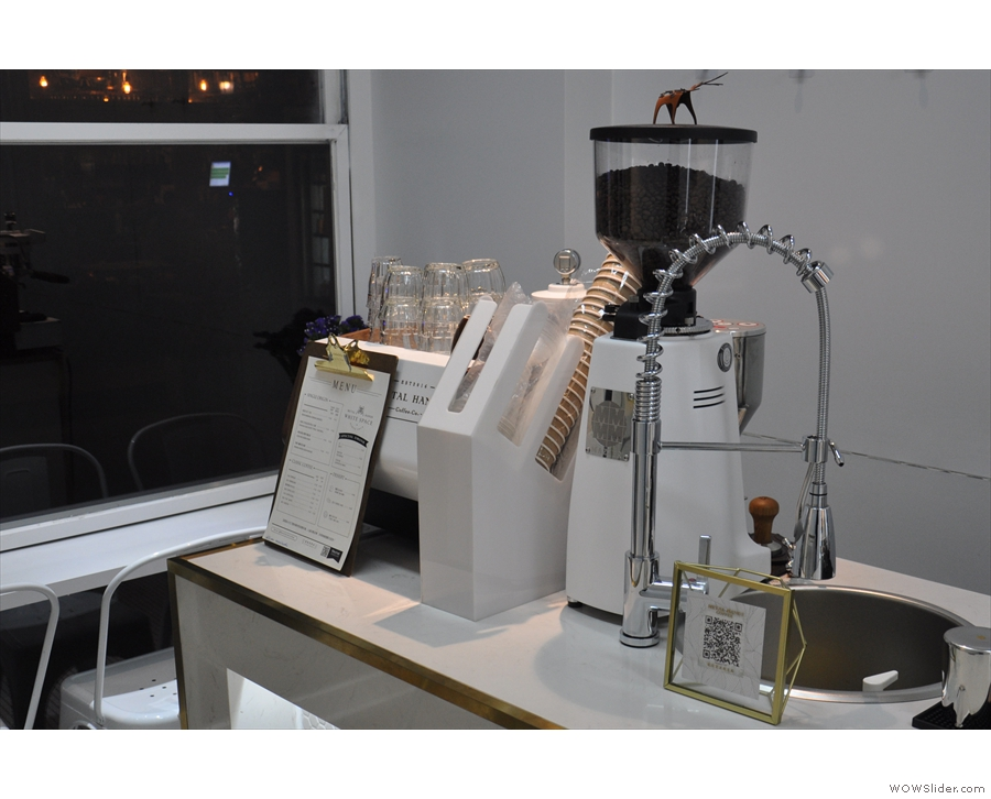 The espresso machine and its grinder are at the start of the counter, along with a menu.