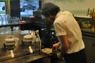 Here's the barista making my 5oz with milk. Step one, grind and tamp the coffee...