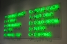 The drinks menu, in green neon, is on the wall behind the counter...