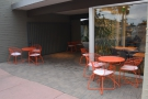 There are four outside tables, all of which shelter in the shade of the shop/passageway.