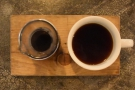 ... which was served in a narrow carafe with a cup on the side, all on a wooden tray.
