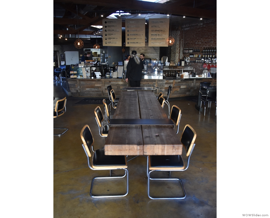 There's a central, long, ten-person comunal table between the door and the counter...