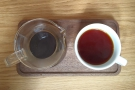 ... in a carafe with a cup on the side, all presented on a wooden tray.