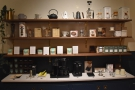 There are retail shelves, opposite the roaster, with the usual mix of coffee kit...