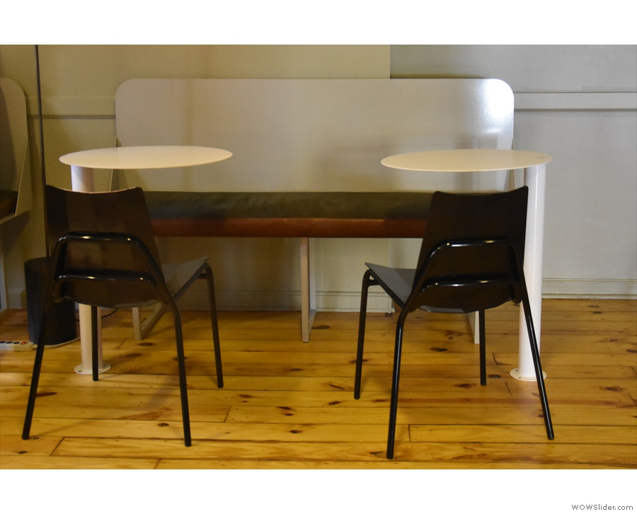 Each has a pair of fixed, round tables, plus an additional chair per table.