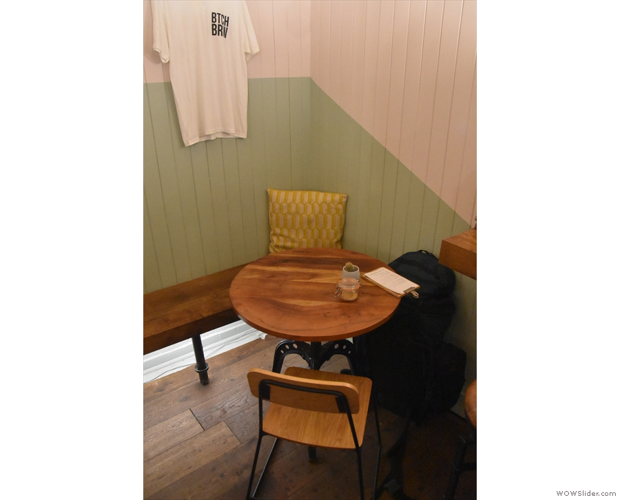A low bench runs along the right-hand wall, with a number of round tables. This one...