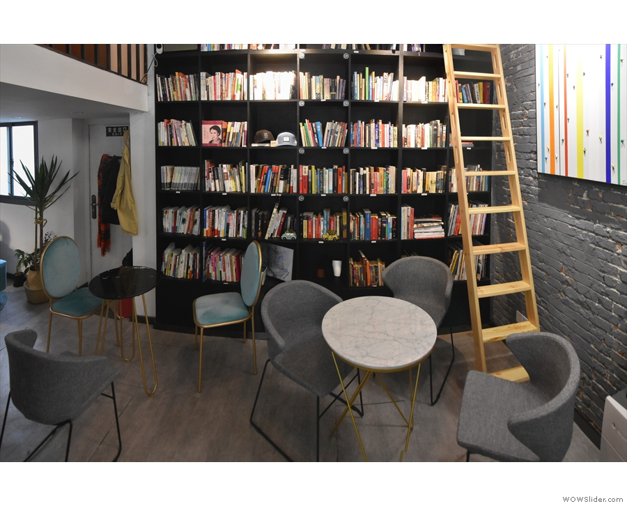 This is followed by a pair of round, three-person tables at the back by the bookshelves.
