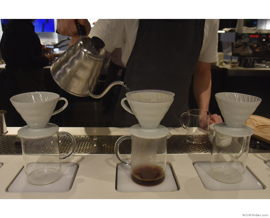... with the barista varying the height of the spout above the surface of the coffee.