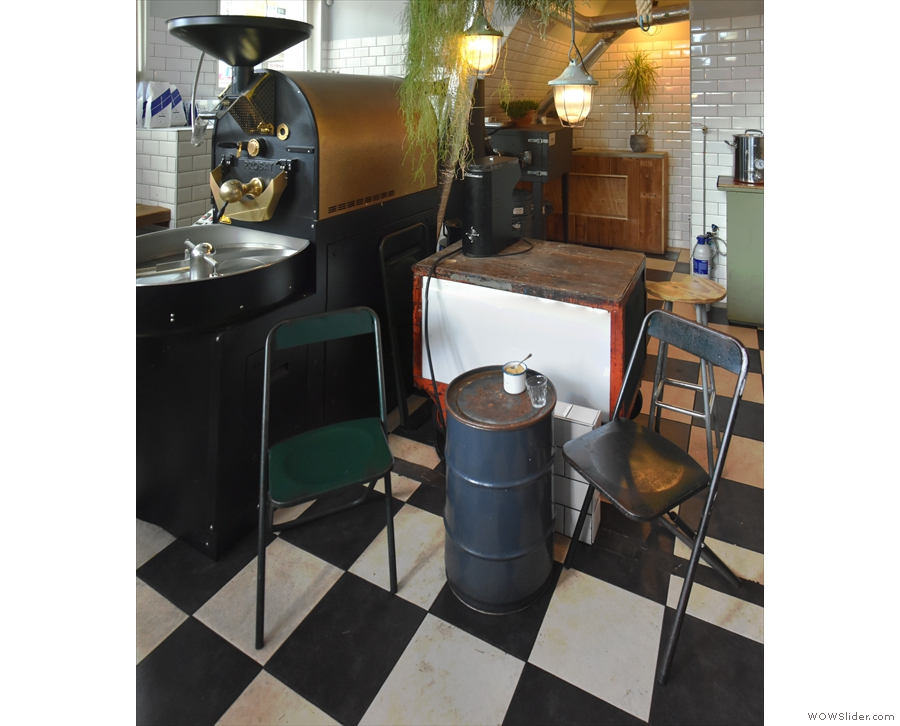 To the right of the roaster is another barrel/coffee table, with a training counter behind.