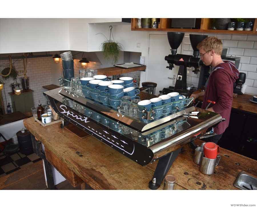 The espresso machine, a sleek Kees van der Westen, is at the far end of the counter.