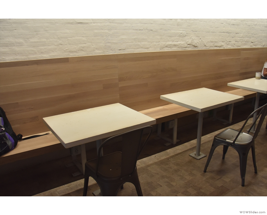 The remaining seating is a line of rectangular two-person tables down the left-hand wall.