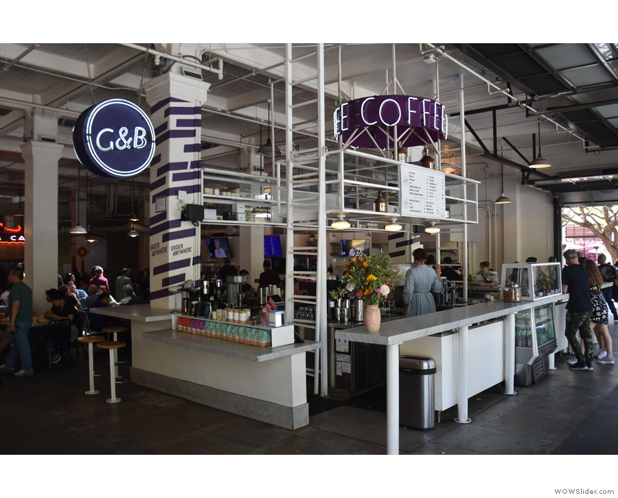 Two stools line the right-hand side, along with a retail section & a standing bar at the back.