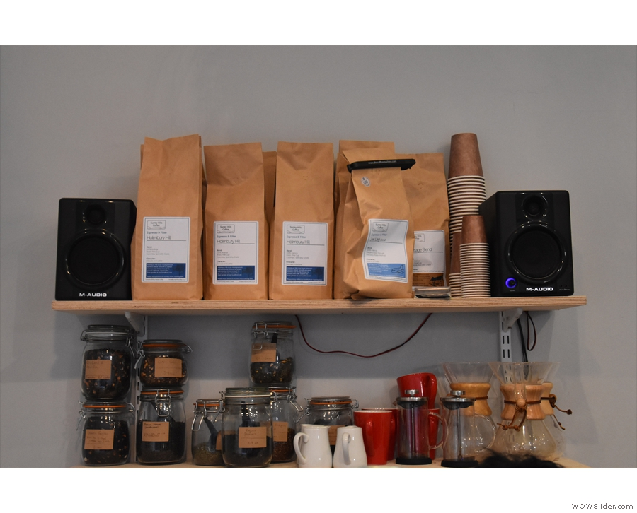 ... with bags of the current coffee on the shelves above.