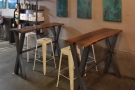 Like the one at the front, these are long, thin trestle tables with high, plastic stools...